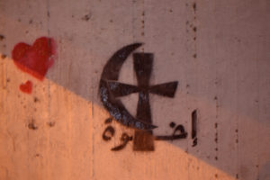 Interreligious dialogue and peace captured in streets in Cairo at the night. On the wall you can see Arabic word 'iida'atan (light). Photo: Barbora Sajmovicova, 2011.