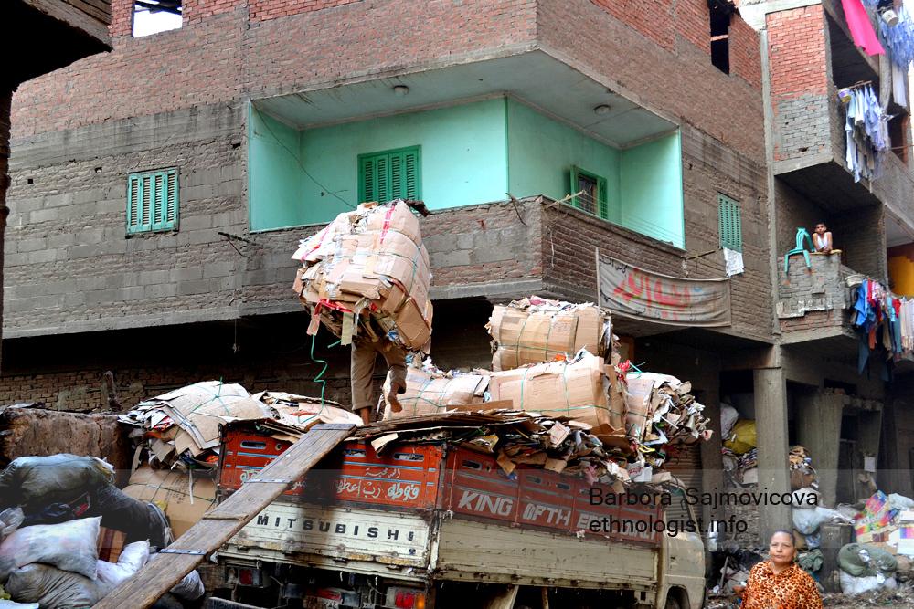 Muž nesoucí na zádech vytříděný papírový náklad na menší nákladní vůz. Foto: Barbora Šajmovičová, 2011.